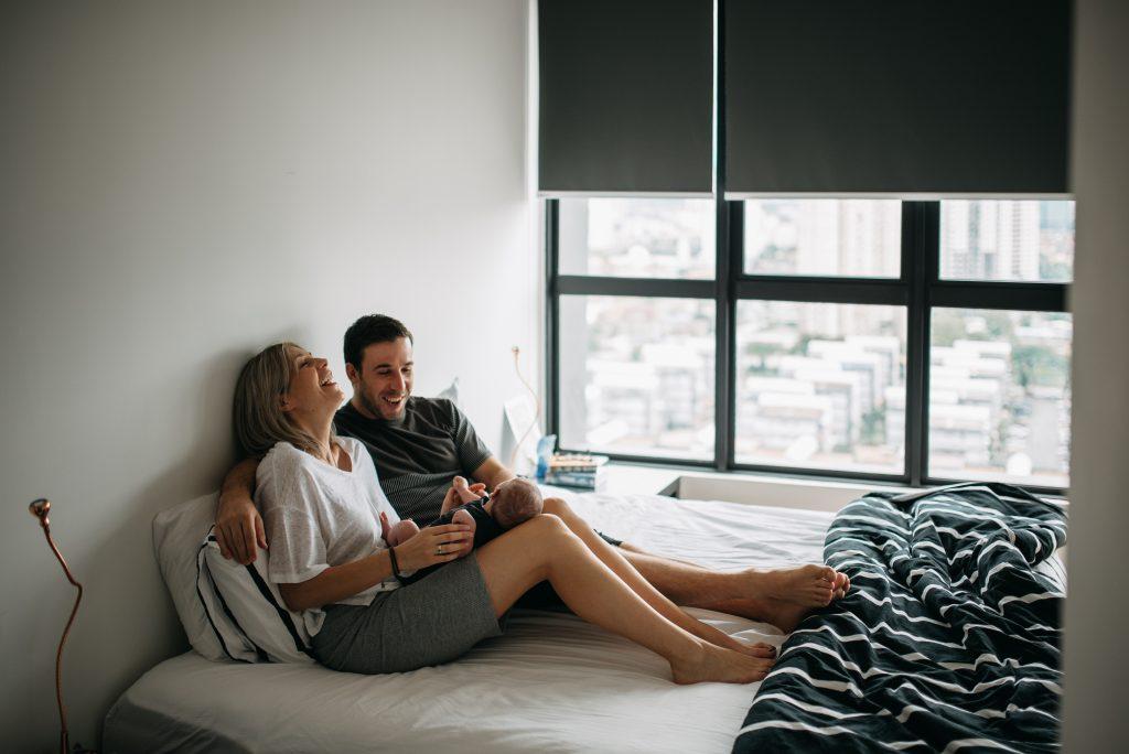moment complice entre nouveaux parents. assis sur leur lit, ils rient en tenant leur nouveau-ne dans les bras.