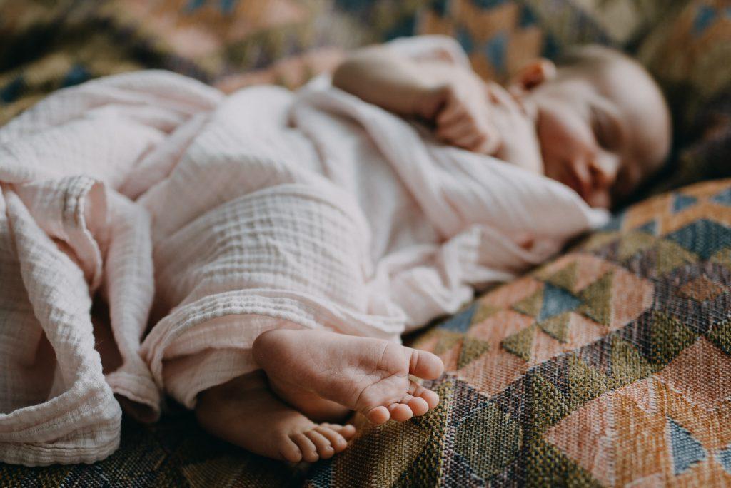 petits pieds nouveau-né en premier plan emmailloté dans un linge rose. Séance Nouveau-né lifestyle à la maison