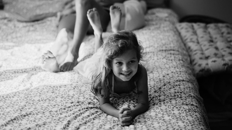 portrait noir et blanc d'une petite fille qui sourit sur un lit