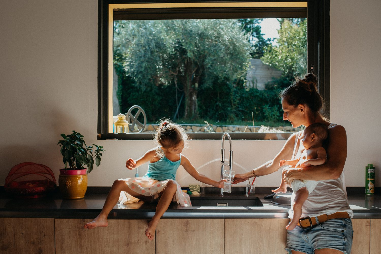 moment authentique de la vie de tous les jours. maman porte son bebe d'une main et aide sa petite fille assise sur le comptoir de la cuisine de l'autre. grande fenetre rectangulaire derriere elle laisse entrer une lumiere magnifique sur les cheveux.