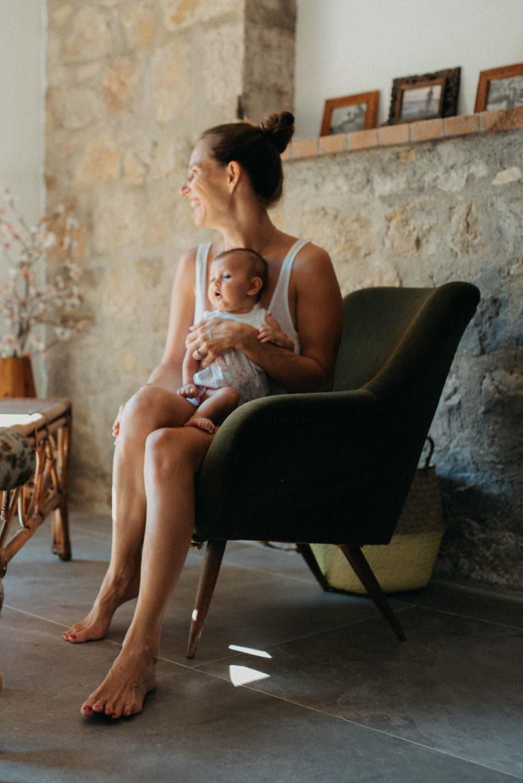 moment calin. maman assise sur un fauteuil vintage vert. elle a son bebe assise sur elle et elle regarde vers la baie vitree en souriant
