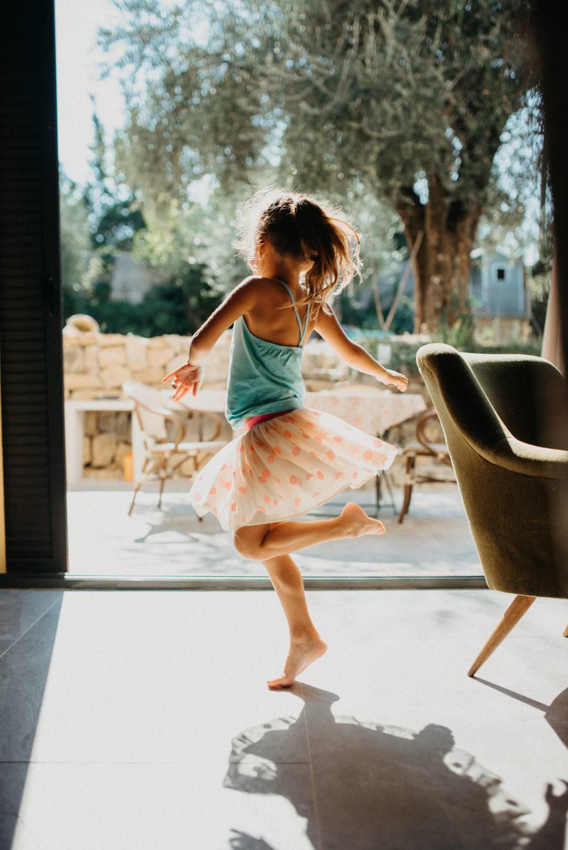 petite fille en mouvement qui danse et fait tourner sa jupe dans une belle lumiere contre-jour. on voit son ombre sur le sol