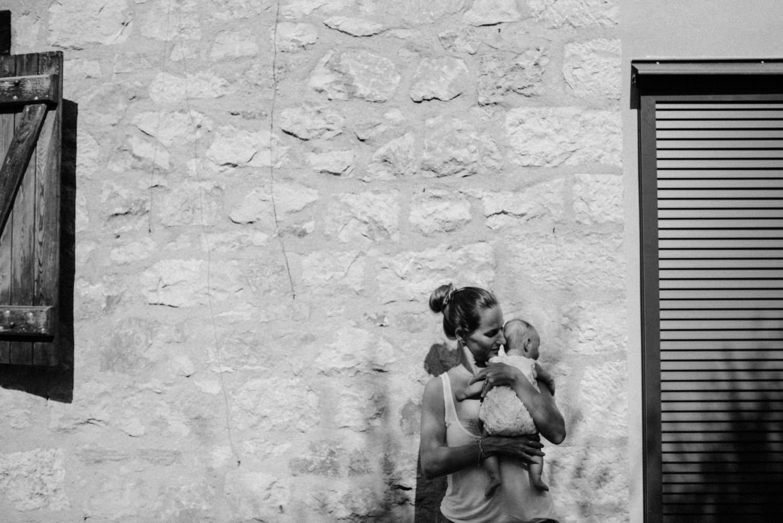 portrait en noir et blanc d'une maman dans une lumiere tachetee, contre un mur qui porte son bebe.