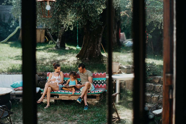 séance famille à la maison. Famille lit un livre ensemble dans leur jardin. la photo est prise de l'intérieur et les portes vitrées encadrent ce moment.