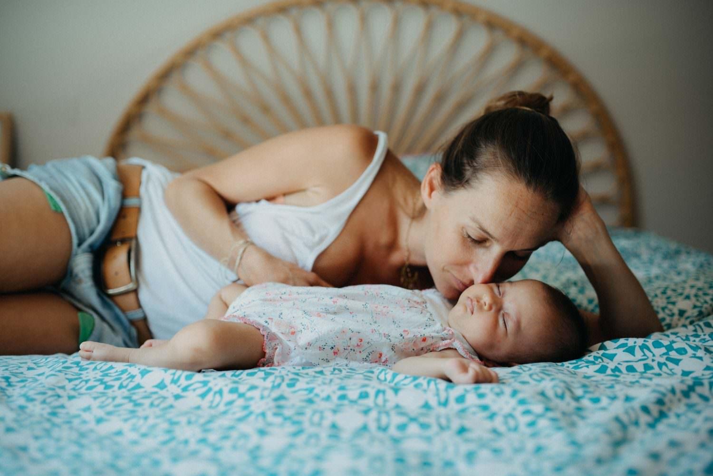 séance famille à la maison. maman allongée sur son côté gauche et penchee sur son bebe qui dort sur le dos, bine pres d'elle. Son nez touche sa joue, comme si elle respirait son bebe.