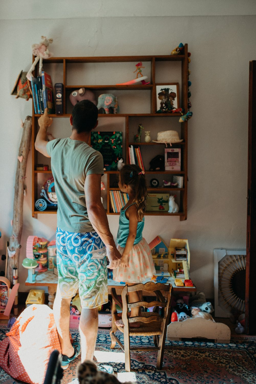 séance famille à la maison. idee de decoration chambre petite fille. Papa choisit un livre pour sa petite fille qui est debout sur une chaise a cote de lui, elle lui tient la main.