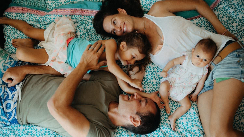 séance famille à la maison. un portrait pris de haut avec maman, papa et les enfants qui sourient en se regardant et se faisant des chatouilles. moment tendre, fort et authentique
