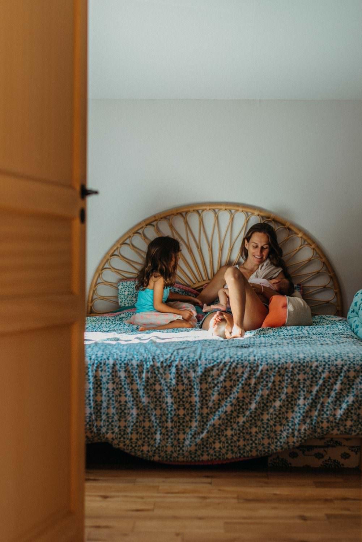 séance famille à la maison. maman allaite son bebe sur son lit dans une jolie lumière reflétée et sourit