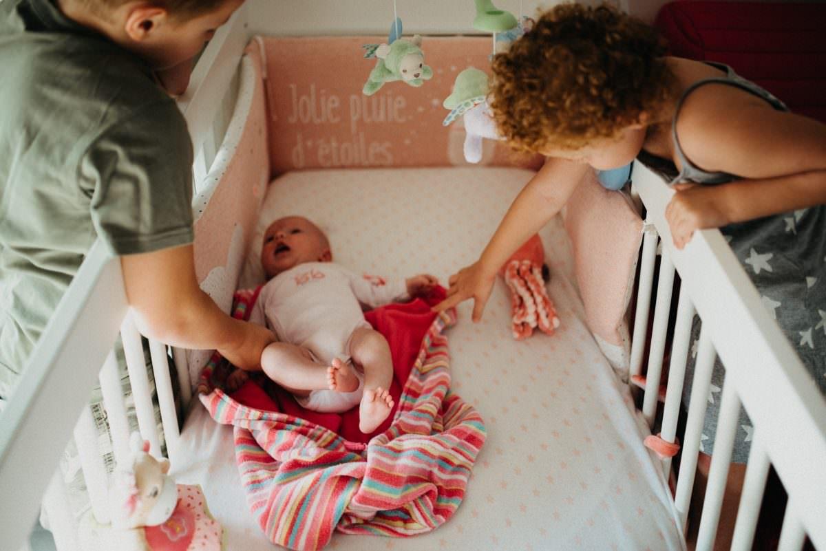 enfants se penchent au dessus d'un berceau avec leur petite soeur dedans pendant une seance famille lifestyle a la maison a Antibes.