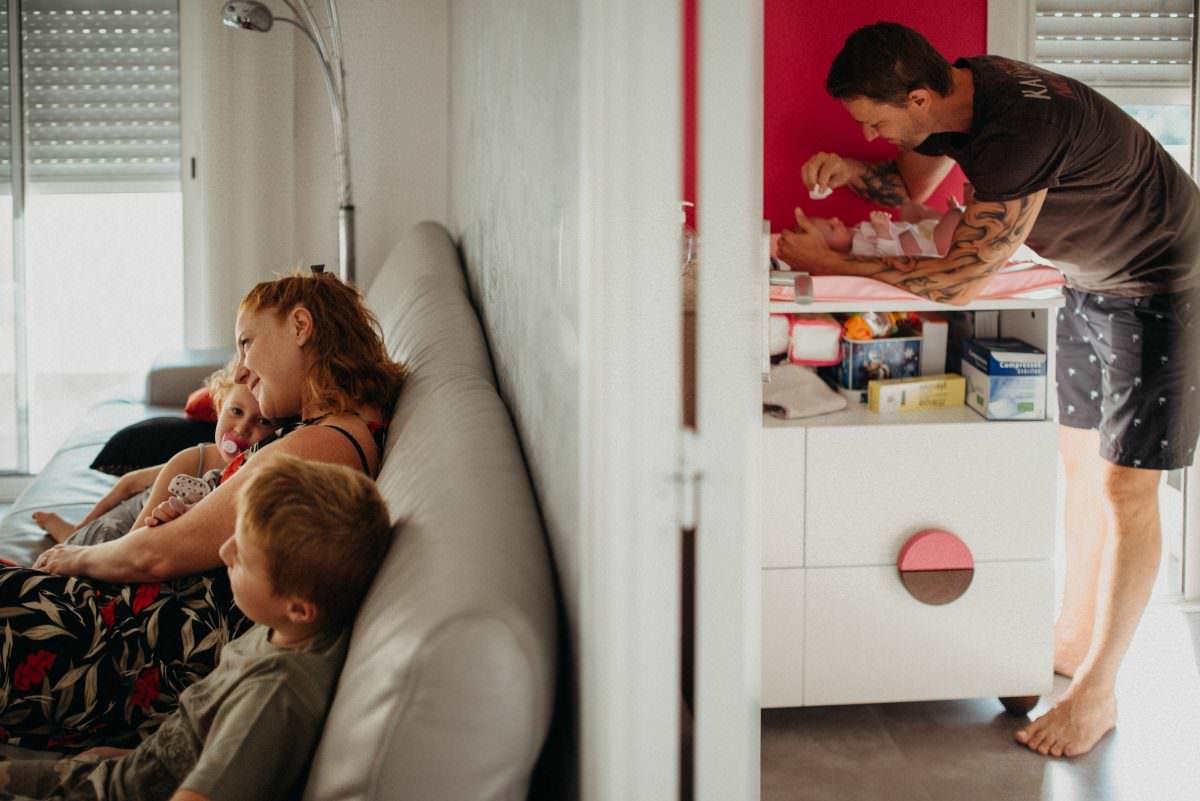 papa est avec bebe dans la piece de droite et La maman est avec les deux autres enfants sur le canape dans la piece de gauche pendant cette seance famille a la maison a antibes