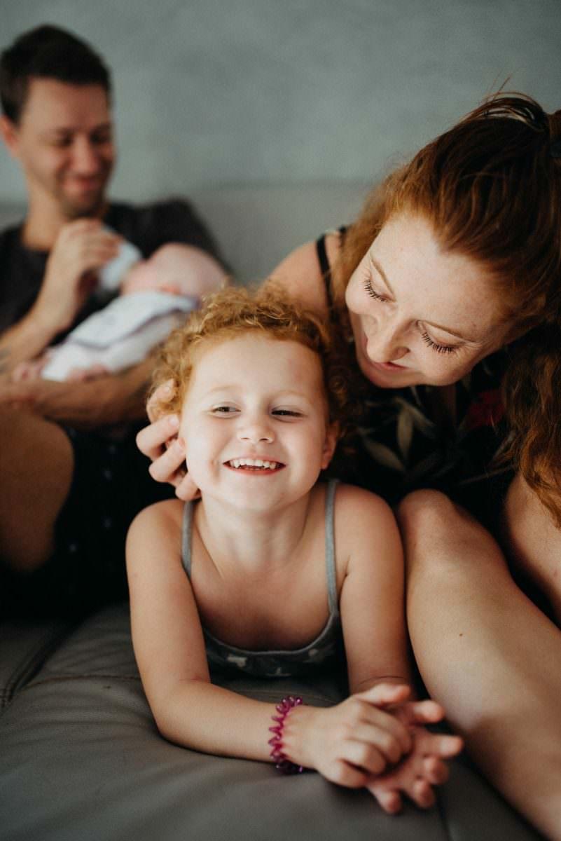 moment caln entre maman et petite fille qui sourit le papa donne le biveron au second plan. Seance lifestyle antibes