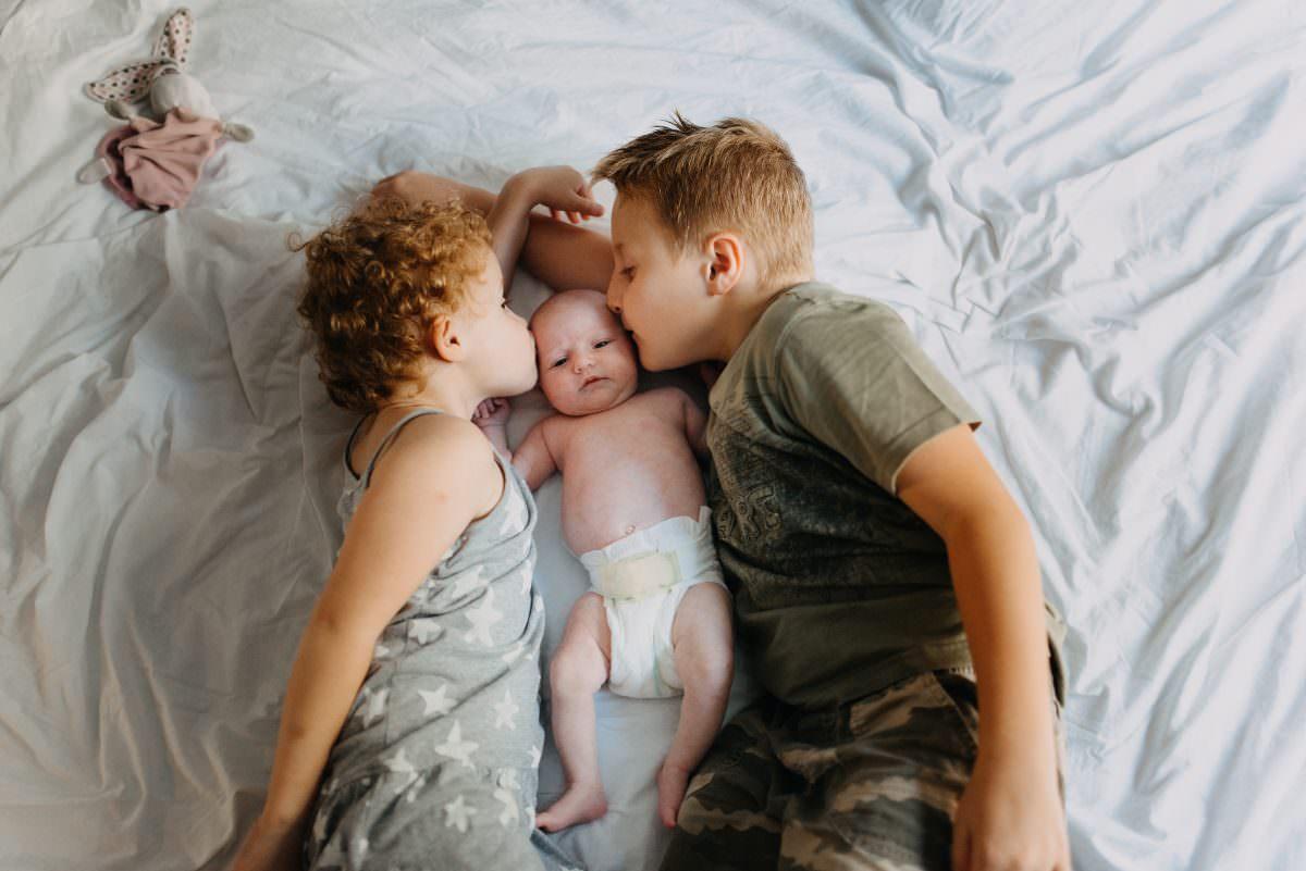 trois enfants sont sur le lit et font un bisou au bebe qui est au milieu