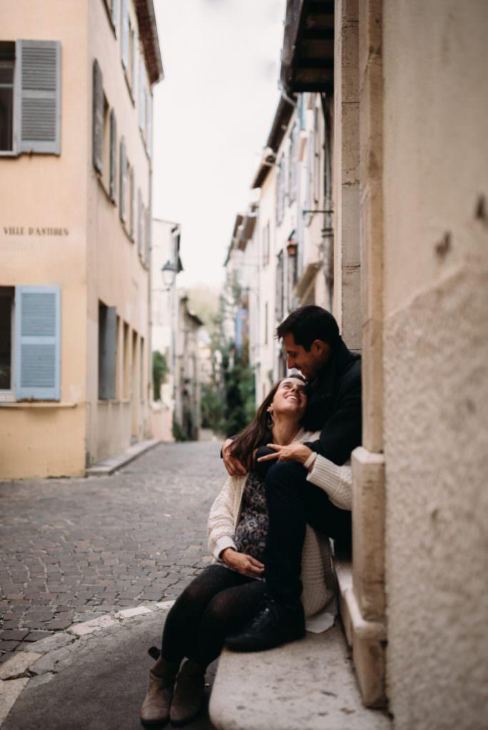 Couple assis sur une marche d'escalier dans une rue du vieil antibes. Le couple sourit et on devine une ruelle avec des paves derriere eux.