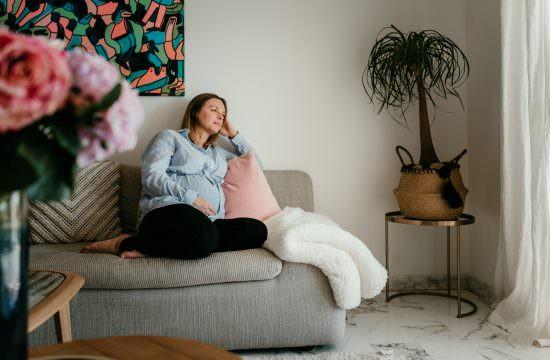 maman assise sur son canape pendant une seance grossesse