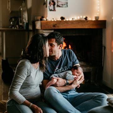 couple, parents pour la premiere fois, assis devant un feu de cheminee, chez eux. le papa porte leur nourrisson dans le sbras.