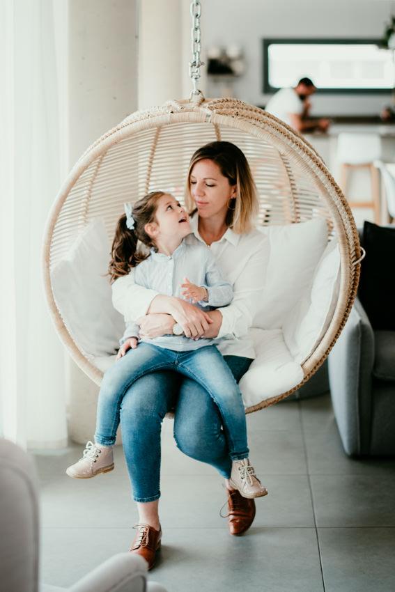 Maman assise dans une balançoire en osier avec sa petite fille sur les genoux. Elles se regardent. La petite fille sourit à sa maman. On y voit beaucoup d'amour dans ce portrait de maman et sa fille.