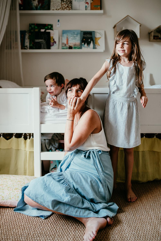 Une maman est assise par terre dans la chambres des enfants. Un petit garcon est allongeé sur le ventre dans le lit derriere elle. la petite fille se tient debout et a sa main sur la bouche de sa maman qui lui fait un bisou.