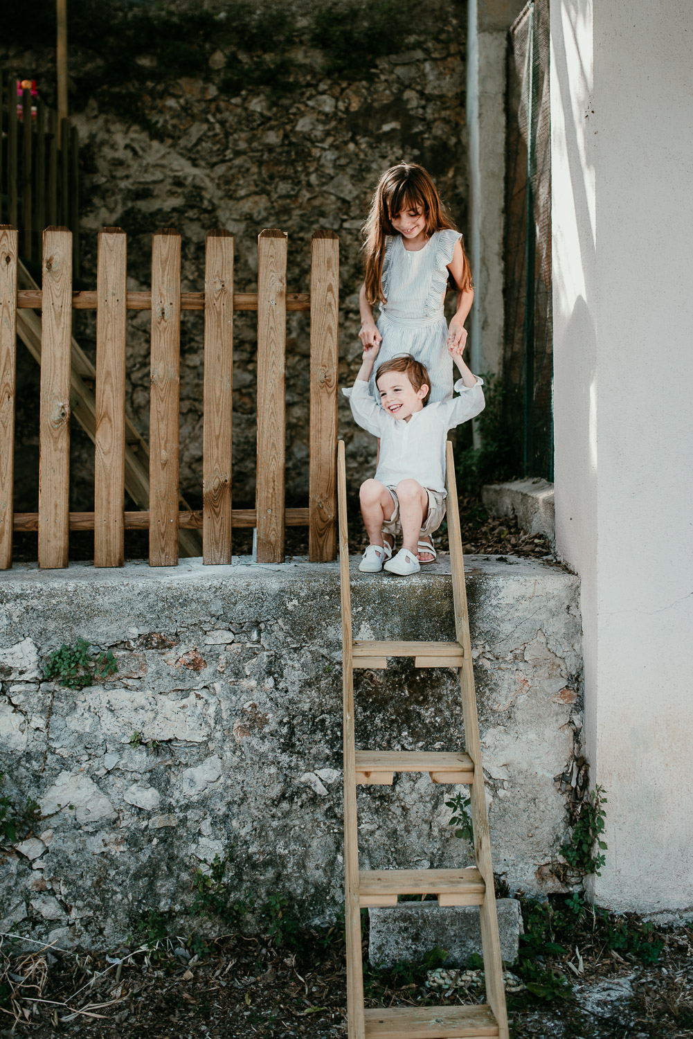 Two children are in their garden. The little boy is sitting on the wall and his feet are on top of a ladder in front of him.His sister is standing behind him. They are holding hands.