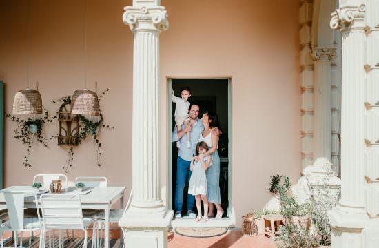 une famille se tient dans la porte d'entree de leur sublime maison. Ils se regardent et se sourient. La petite fille est debout devant sa maman et lui prend la main. Le petit garcon est sur les épaules de son père.