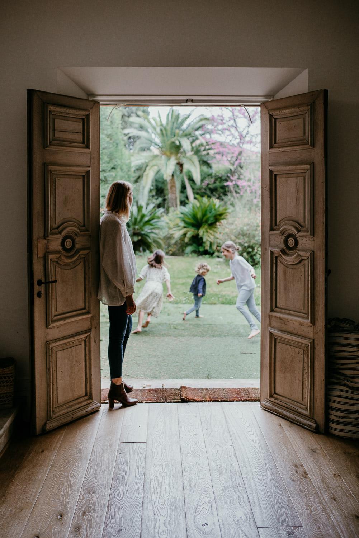 une scene e la vie de tous les jours pendant cette seance famille. la photo est prise de l'interieur. La maman est adossee a une superbe porte en bois et regarde dehors. Elle regarde ses trois enfants qui courent dans le jardin en cercle. C'est une image equilibree en composition et très efficace.