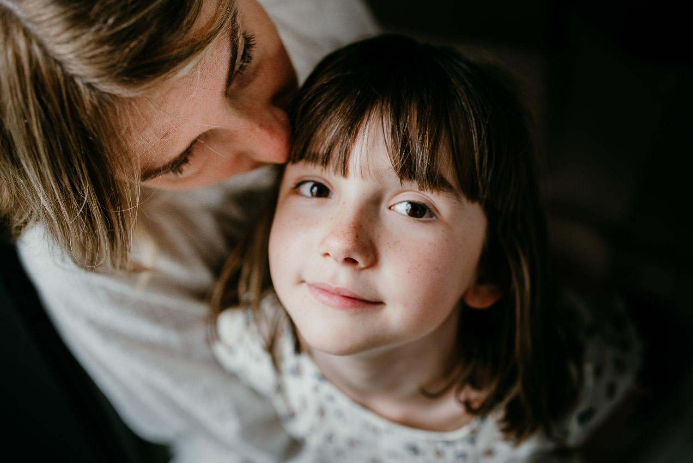 portrait d'une petite fille qui regarde la photographe. La photo est prise de près. Elle a les yeux marron et des jolies taches de rousseur sur ses joues et son petit nez. Sa maman lui fait un bisou sur la tempe.