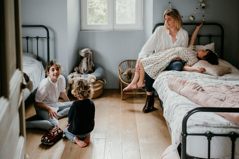 image qui se passe dans une chambre d'enfants. la famille est faite de la maman et de ses trois enfants. la maman est assise sur un des deux lits. Sur elle, une petite fille est allongée. sur le sol, la plus grande joue avec son petit frère.