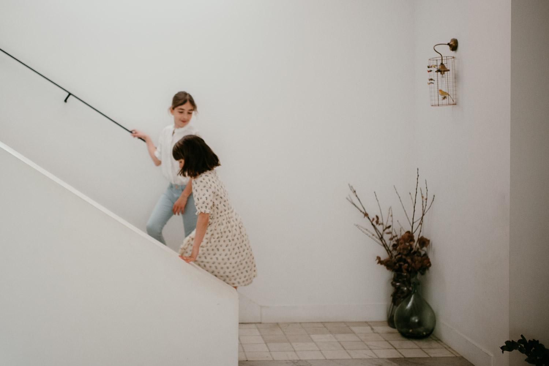 deux petites filles s'appretent a monter un escalier. La photo est graphique et on perçoit le mouvement des deux fillettes.