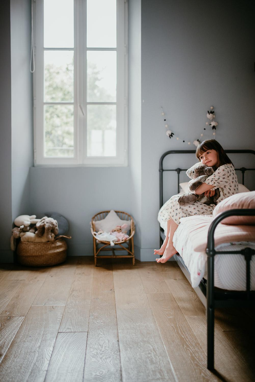 image en portrait pour cette photo de seance famille. Une petit fille est assise sur son lit. Elle caline sa peluche. Ses pieds ne touchent pas par terre, ce qui indique son jeune age. Il y a une grande fenetre du cote gauche et en dessous une petit chaise et un panier rempli de peluches.