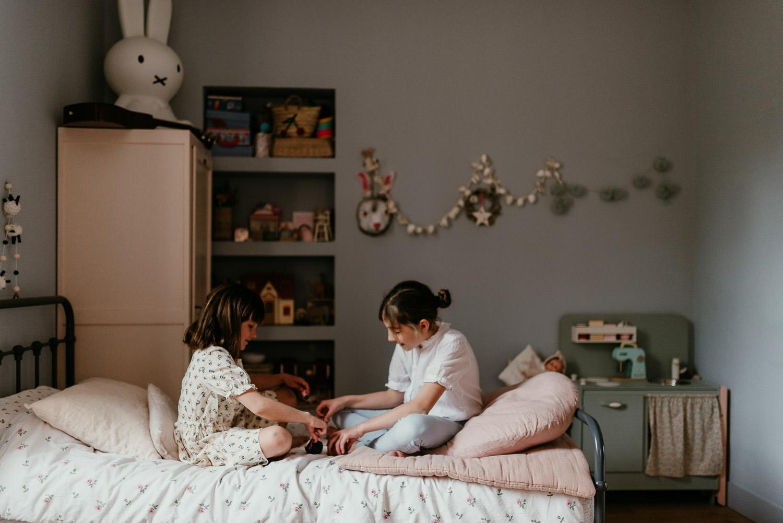 une image de seance famille ou les deux soeurs sont assises sur le lit de l'un d'entre elles. Elles jouent ensemble. On voit aussi la decoration de la chambre avec une petie cuisine vintage en bois.