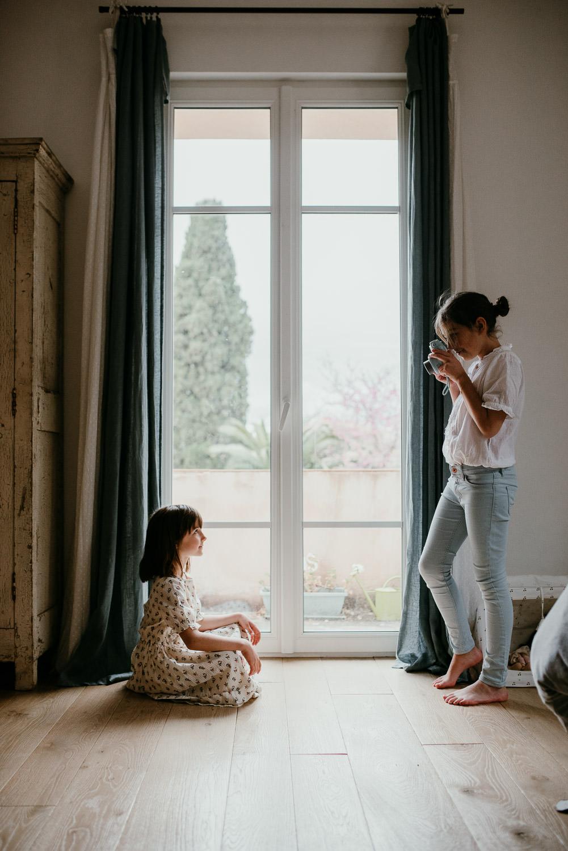Une photo de famille faite des deux soeurs. Elles se trouvent d'un cote et de l'autre d'une grande et belle porte fenetre. L'une est assise en tailleur et regarde sa grande soeur, debout qui la prend en photo avec son polaroid.