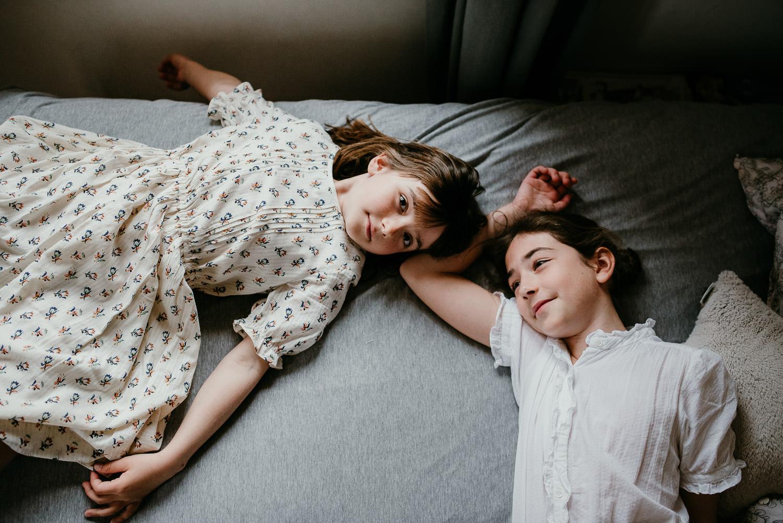 un joli moment de famille entre les deux soeurs allongees sur un lit