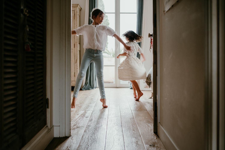 deux petites filles qui dansent pendant une seance famille a la maison, a Cannes. on perçoit le mouvement de la danse La photo est prise en dehors de la piece dans laquelle les filles se trouvent. C'est une image graphique et equilibree dans sa composition, la lumiere en contre-jour est douce.