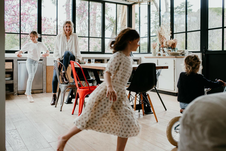 Pendant une seance famille a Cannes, on se retrouve dans la grande cuisine. La maman est assise sur la table et est en focus. les trois enfants dansetn, courent et font du velo autour la table. La maman sourit de cette scene joyeuse.
