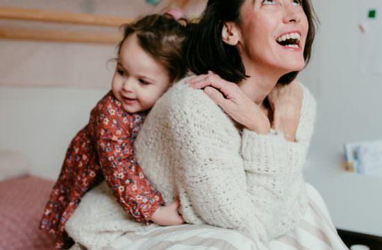 Portrait tendre d'une maman et sa petite fille. la maman est accroupie et sa petite fille l'enlace, alors qu'elle est debout derriere elle. la maman sourit en regardant en l'air. Elle a l'air tellement heureuse.