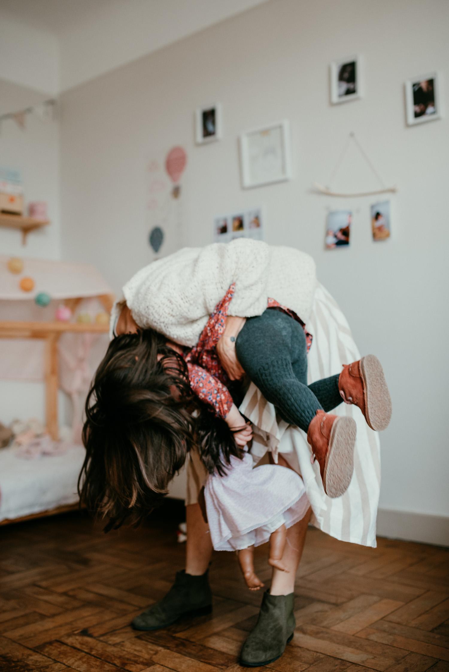 Une maman et sa fille joue et se chatouille.On voit les pieds de la petite fille qui est renversée par sa maman. Elles rient toutes les deux