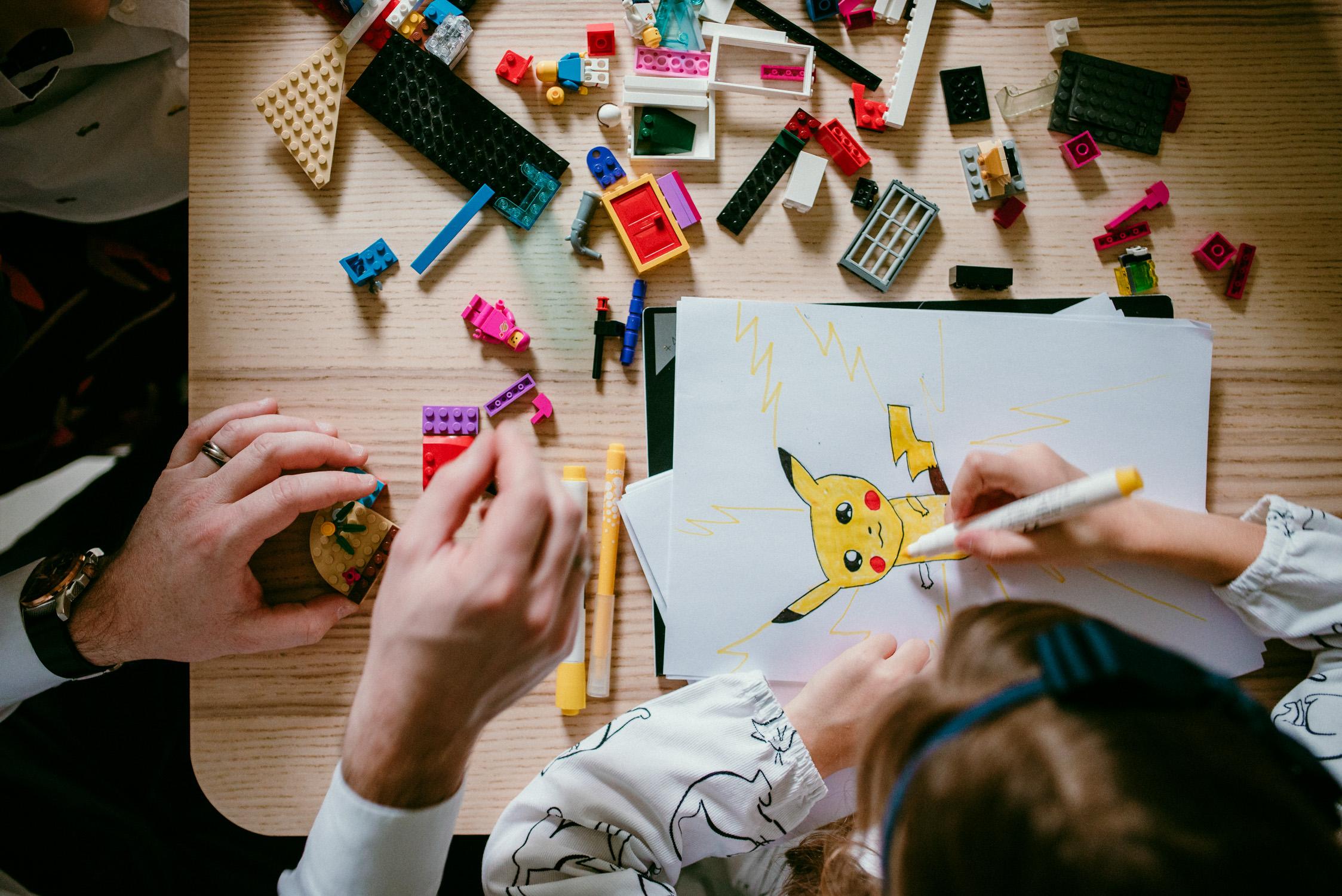 c'est une photo prise de dessus. on y voit des legos, des mains et le dessin qu'a fait la petite fille.