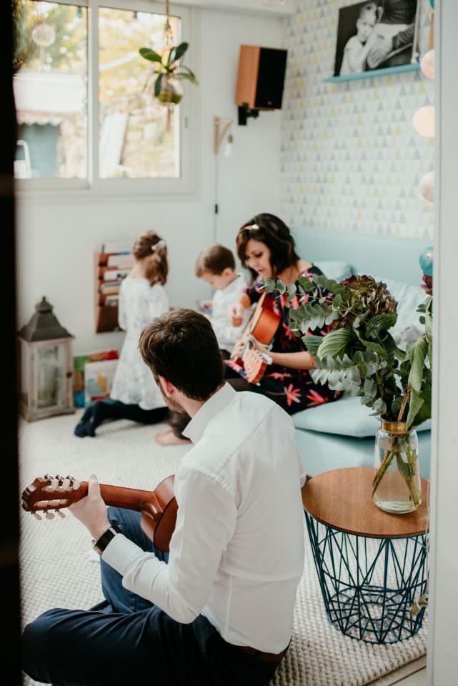 une famille est dans son salon. les enfants jouent en arriere plan et le couple est devant et jouent de la guitare. Ils chantent. Prace que la plante est en focus au premier plan, on a l'impression que l'on est en retrait de la scene et qu'on respecte leur intimité