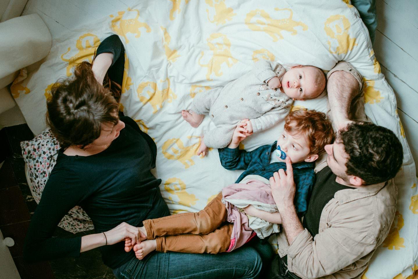 portrait de famille a domcile. Ils sont tous les 4 par terre, sur un duvet. les enfants sont allonges et les parents les regardent avec amour.