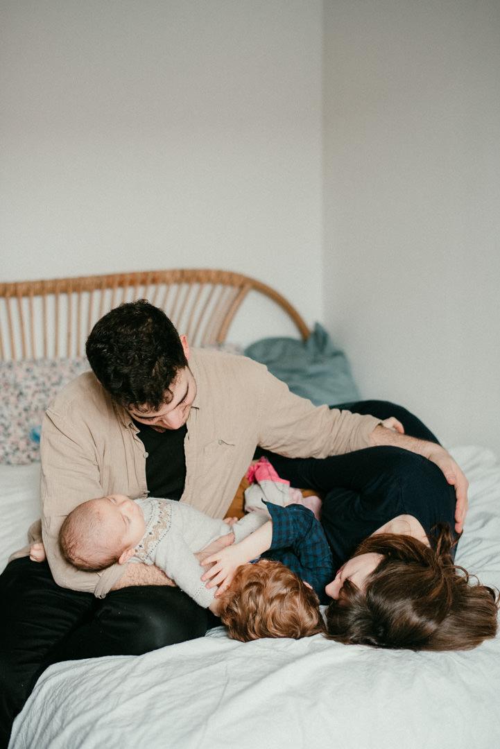 portrait de famille. le papa est assis ur le lit et porte un bebe qui dort sur son bras droit. sa femme et son autre enfant sont allongés. le bras gauche du papa enlace sa femme.