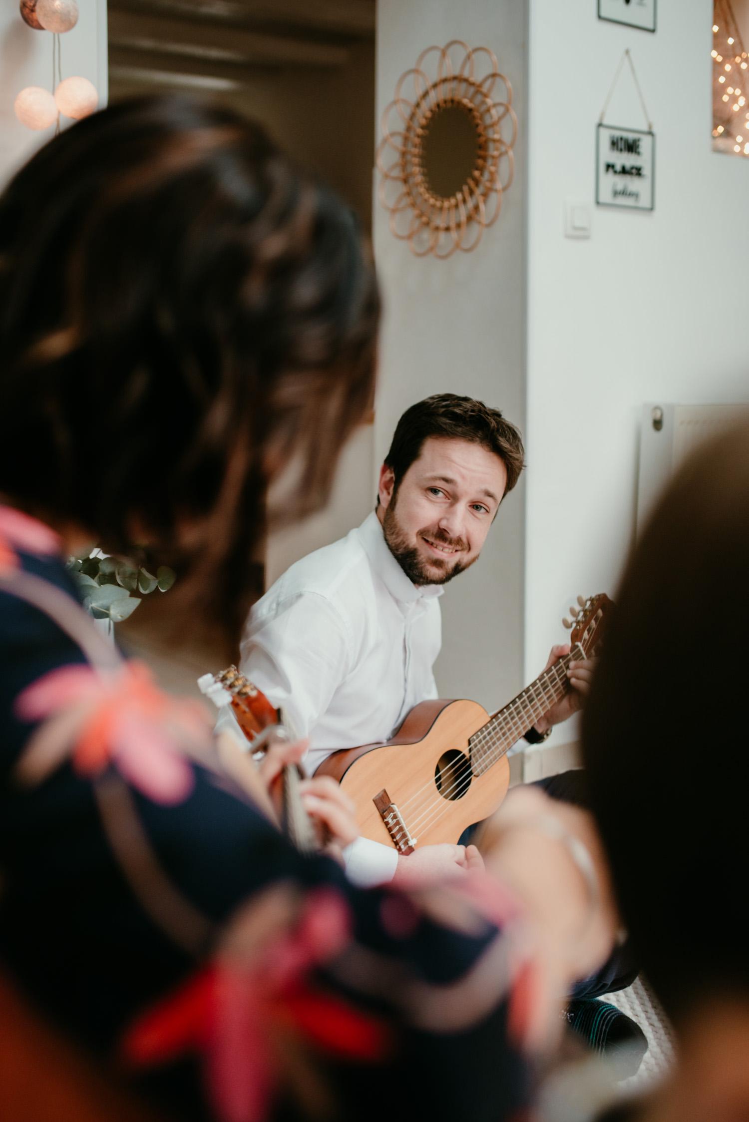 homme joue de la guitare en regardant vers sa femme pendant une seance famille