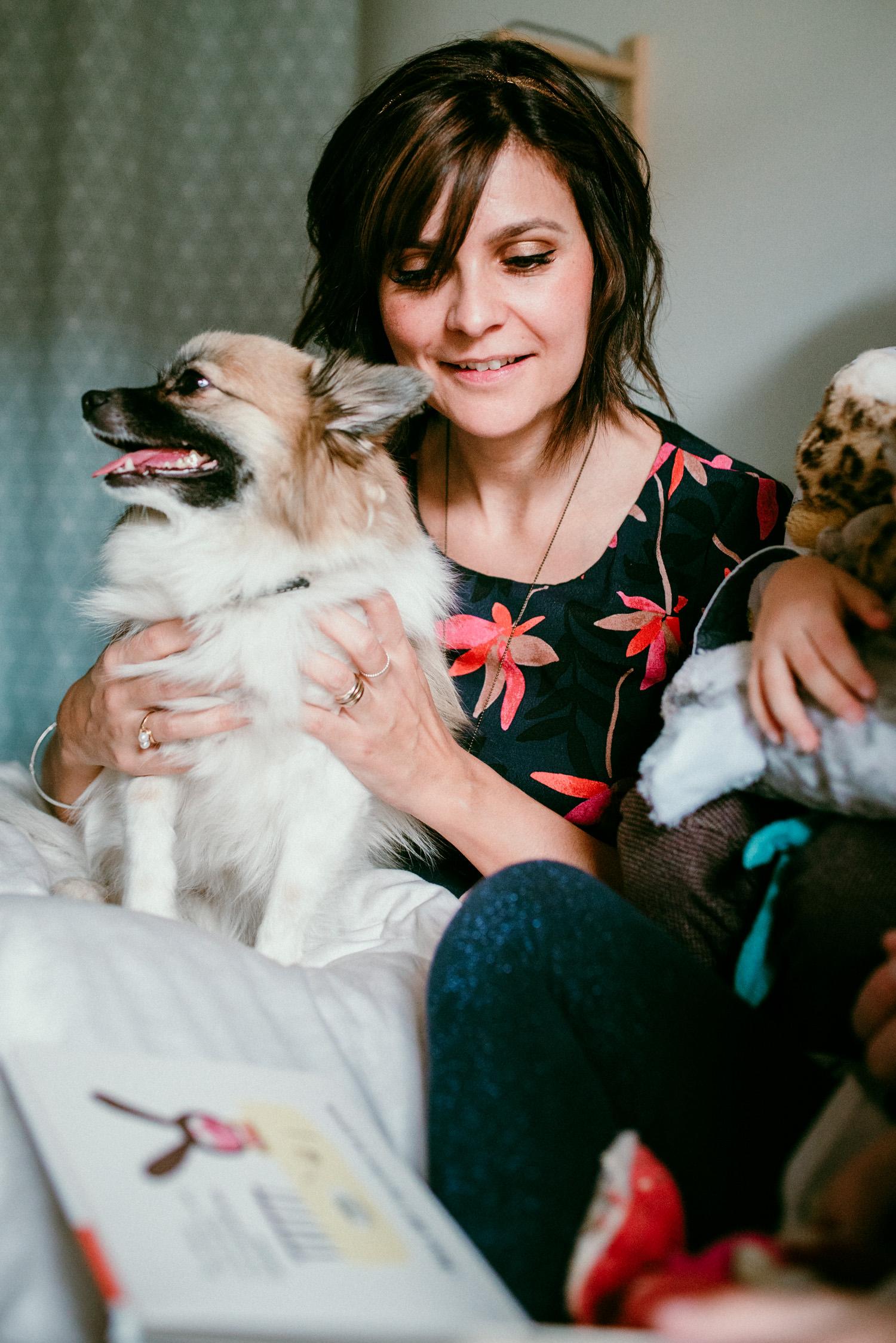 une femme sourit legerement en regardant un livre posé devant elle, elle a les mains autour de sont petit chien. On devine un enfant qui lit lors de cette seance famille lifestyle a domicile