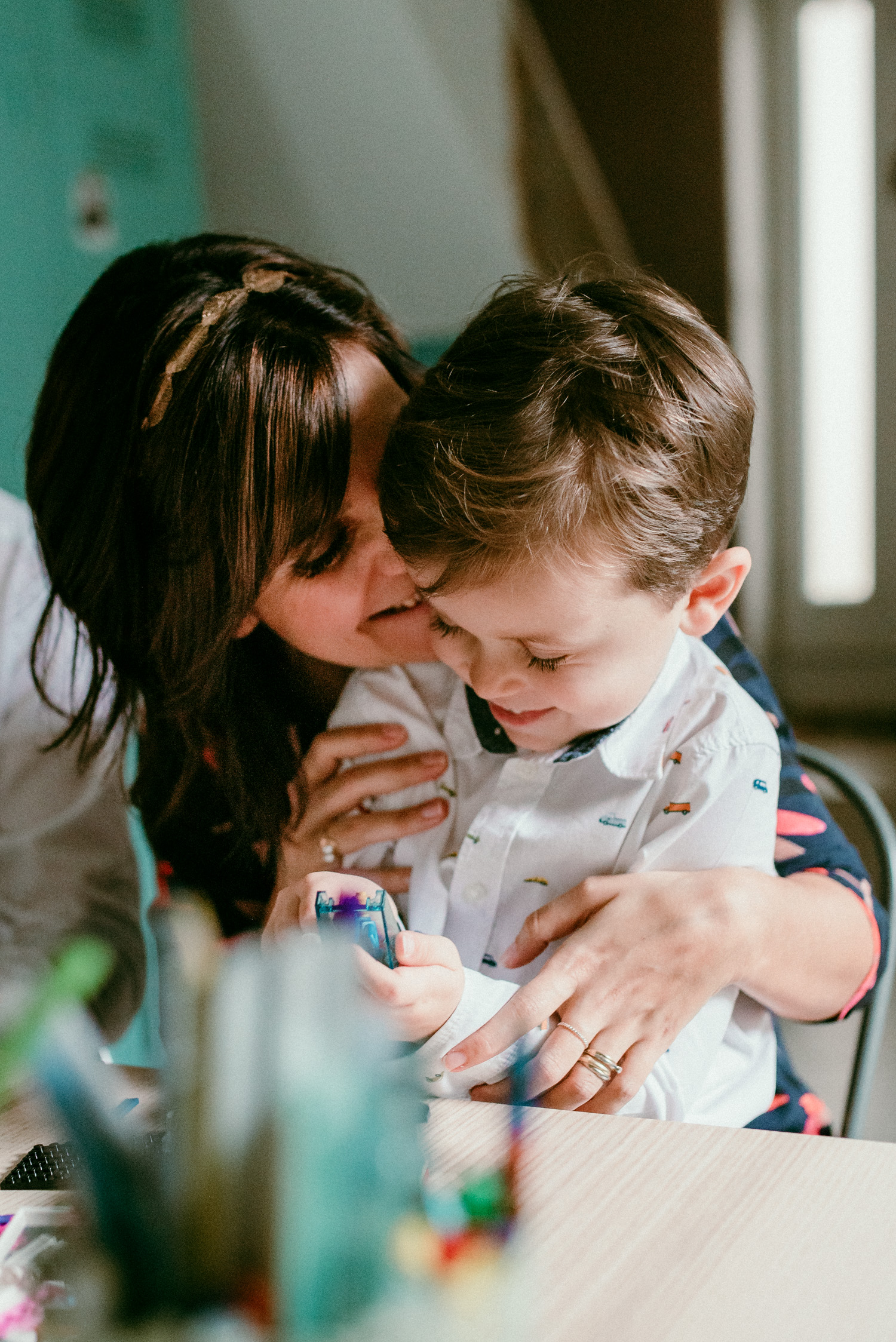 une maman et son fils sourient, la maman lui fait un câlin. Ils sont proches et ont une relation très spéciale et cela se voit.