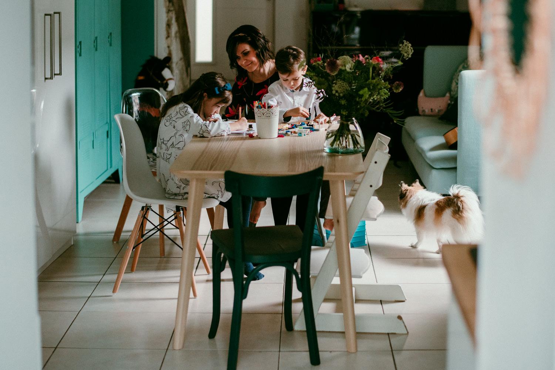 une maman est ses deux enfants sont assis a la table de la cuisine. La petite fille dessine et le petit garcon aussi. La maman regarde sa fille en souriant. Ils sont dans une jolie lumiere de cote. la photogrpahe est Caro Cuinet Wellings