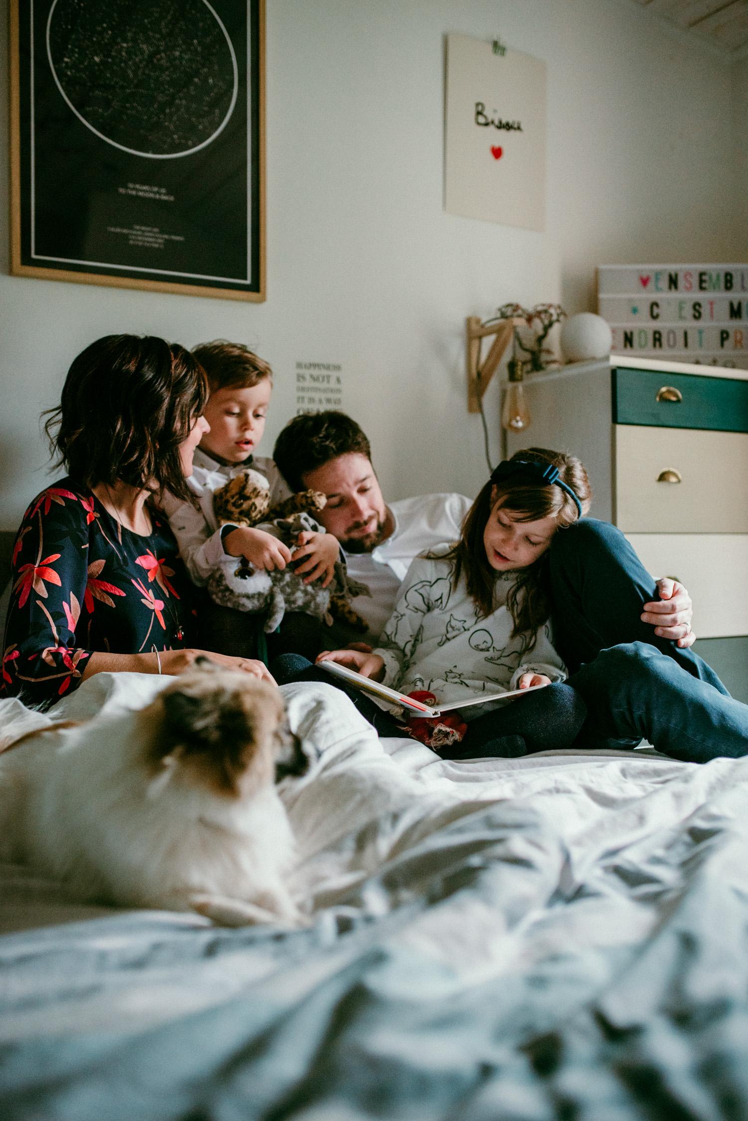 portrait fait sur le lit pendant une seance famille à domicile. On y voit 2 enfants et les parents, tous connectés.