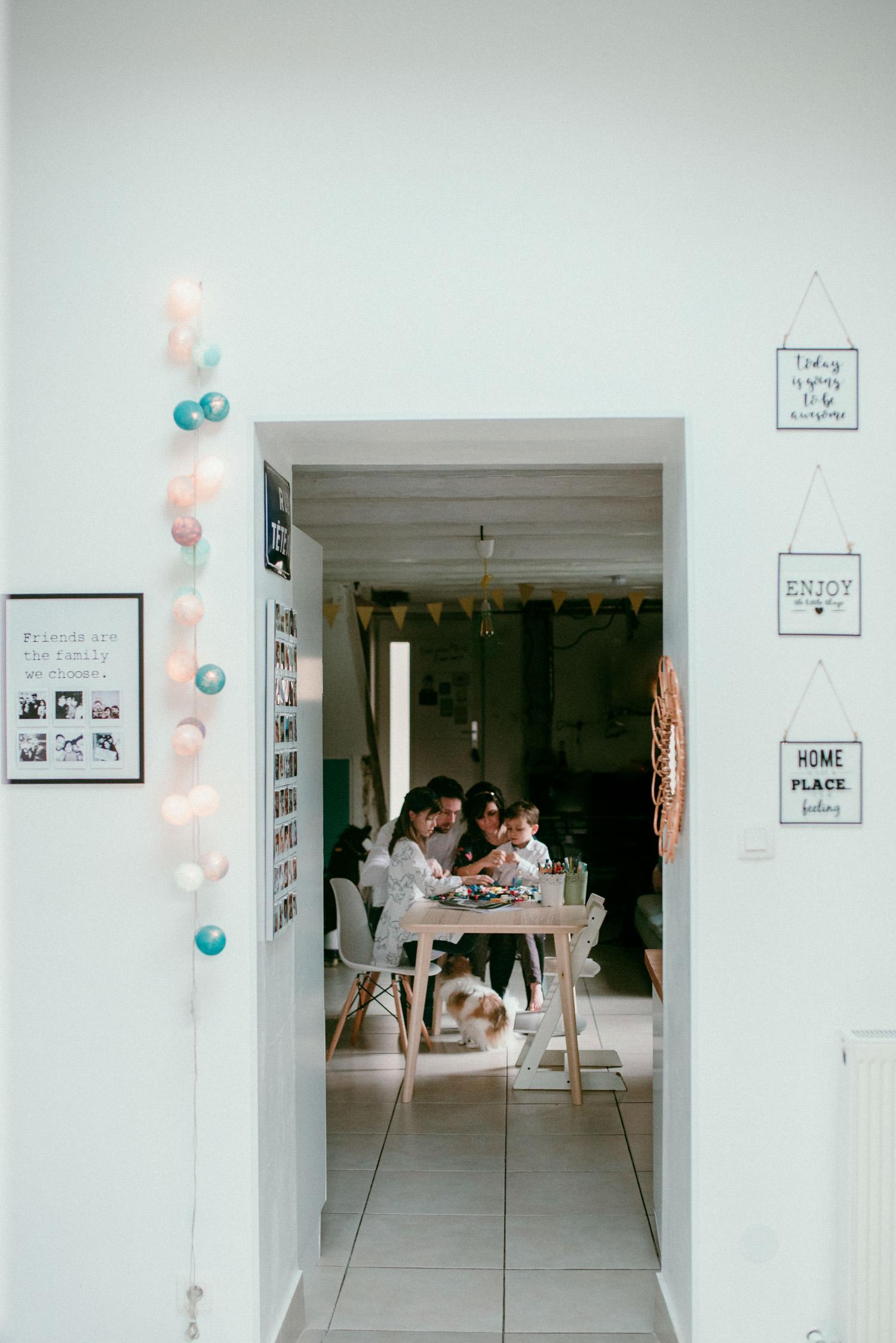 Une famille est assise a la table et joue ensemble pendant une seance photo lifestyle