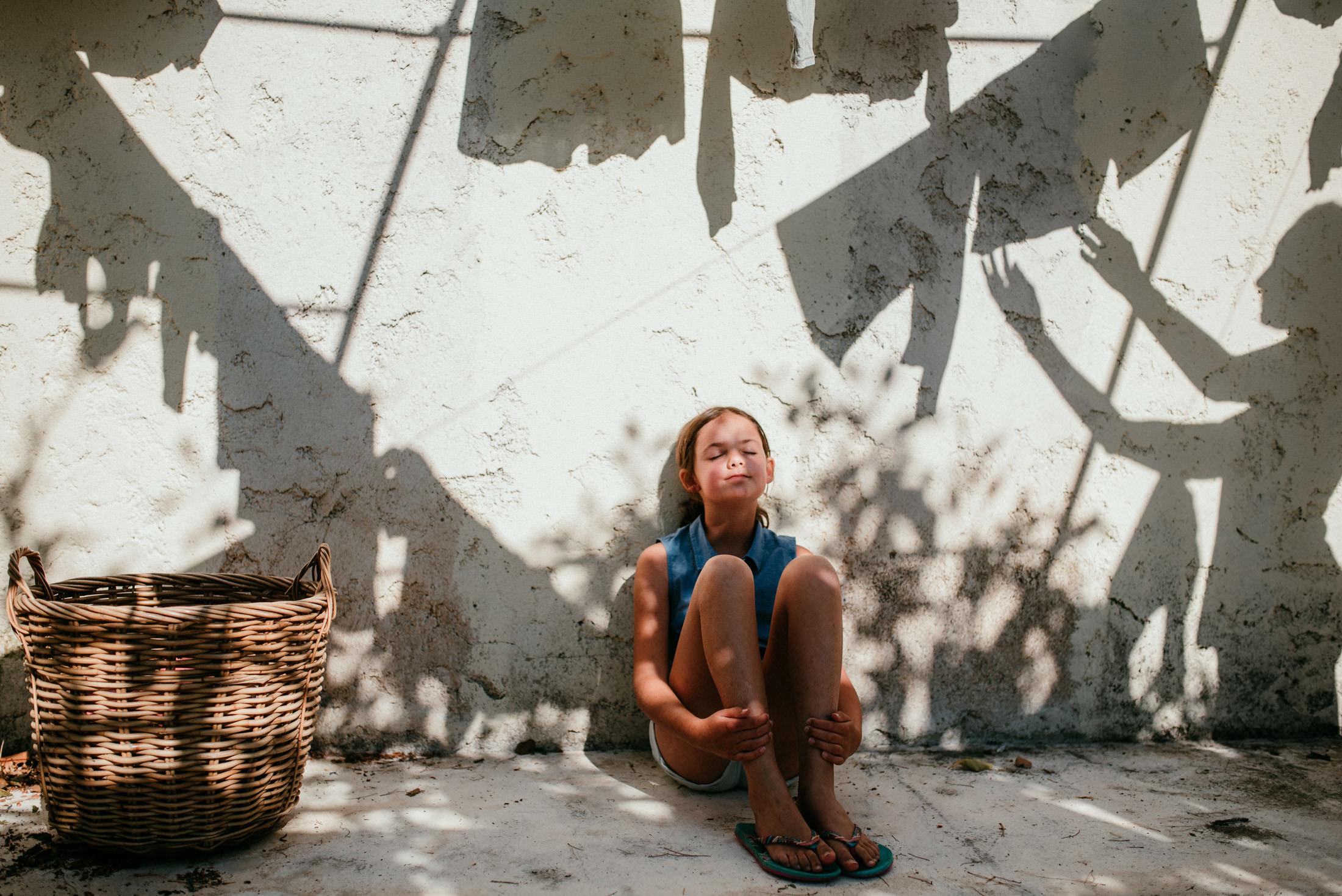petite fille assise au milieu du linge etendu