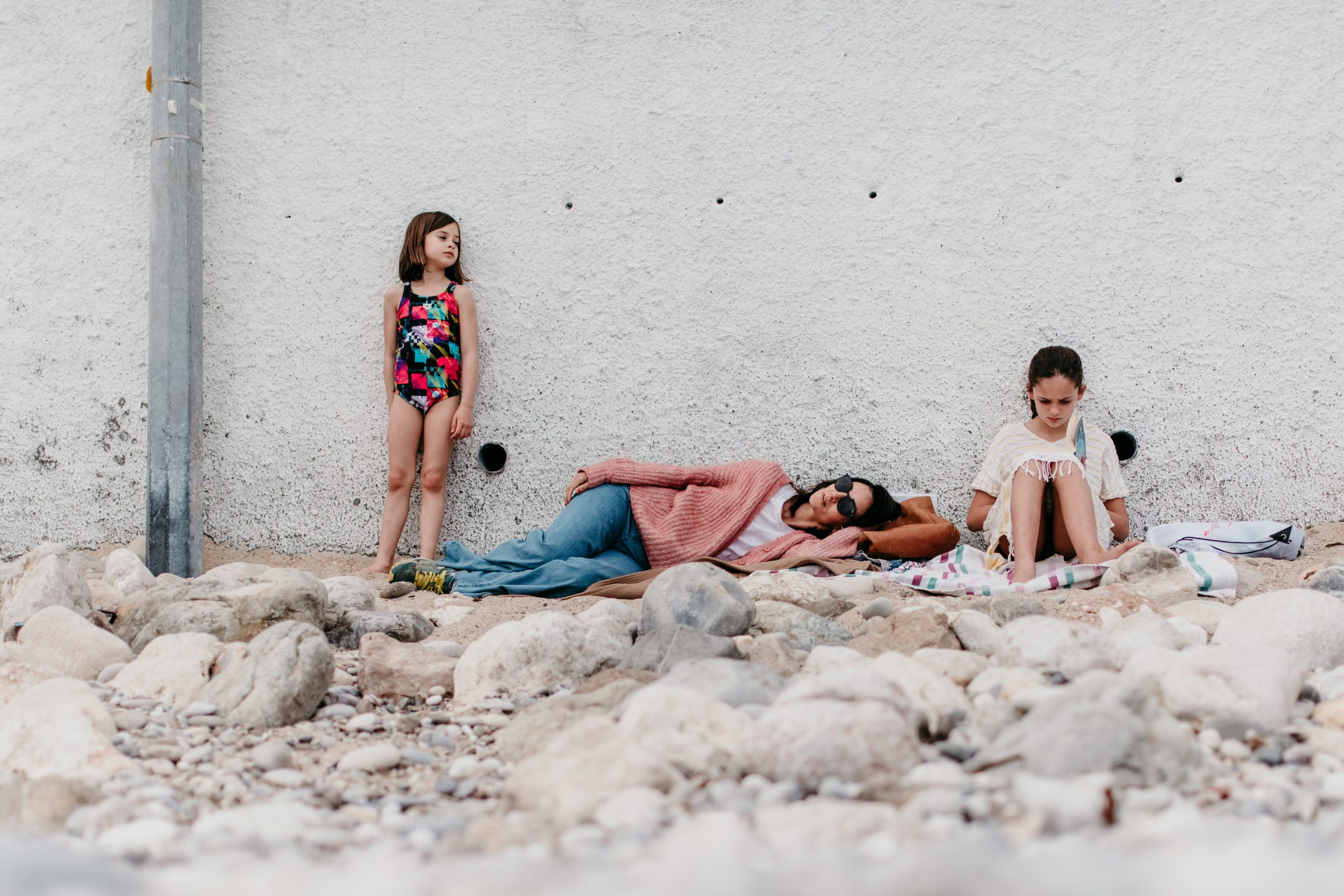 little girl in a swimsuit standing against a wall. mum is lying down and a teen girl sitting and reading her book on a beach french riviera
