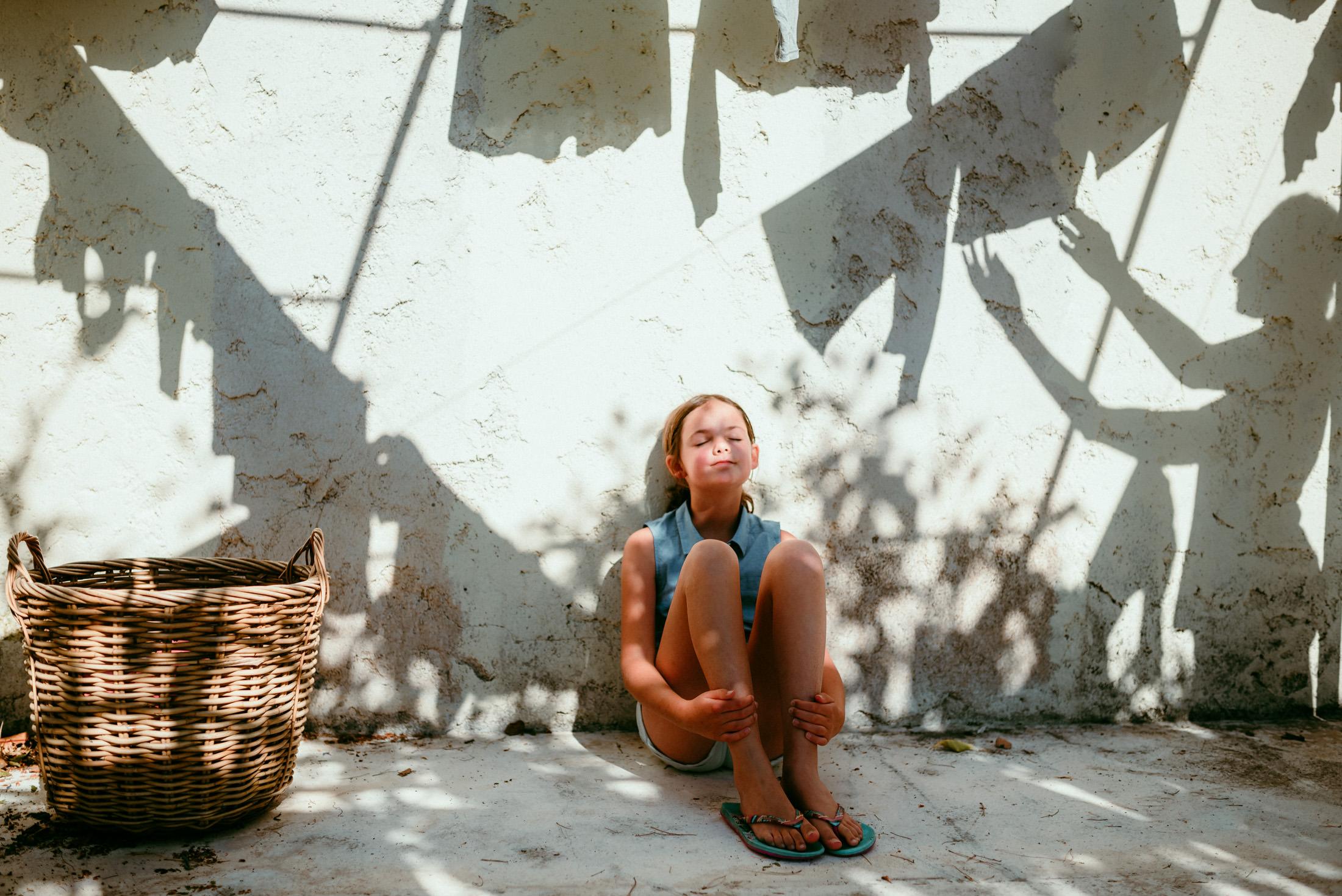 petite fill assise sur le sol, au soleil, entouree d'ombres de linge etendu