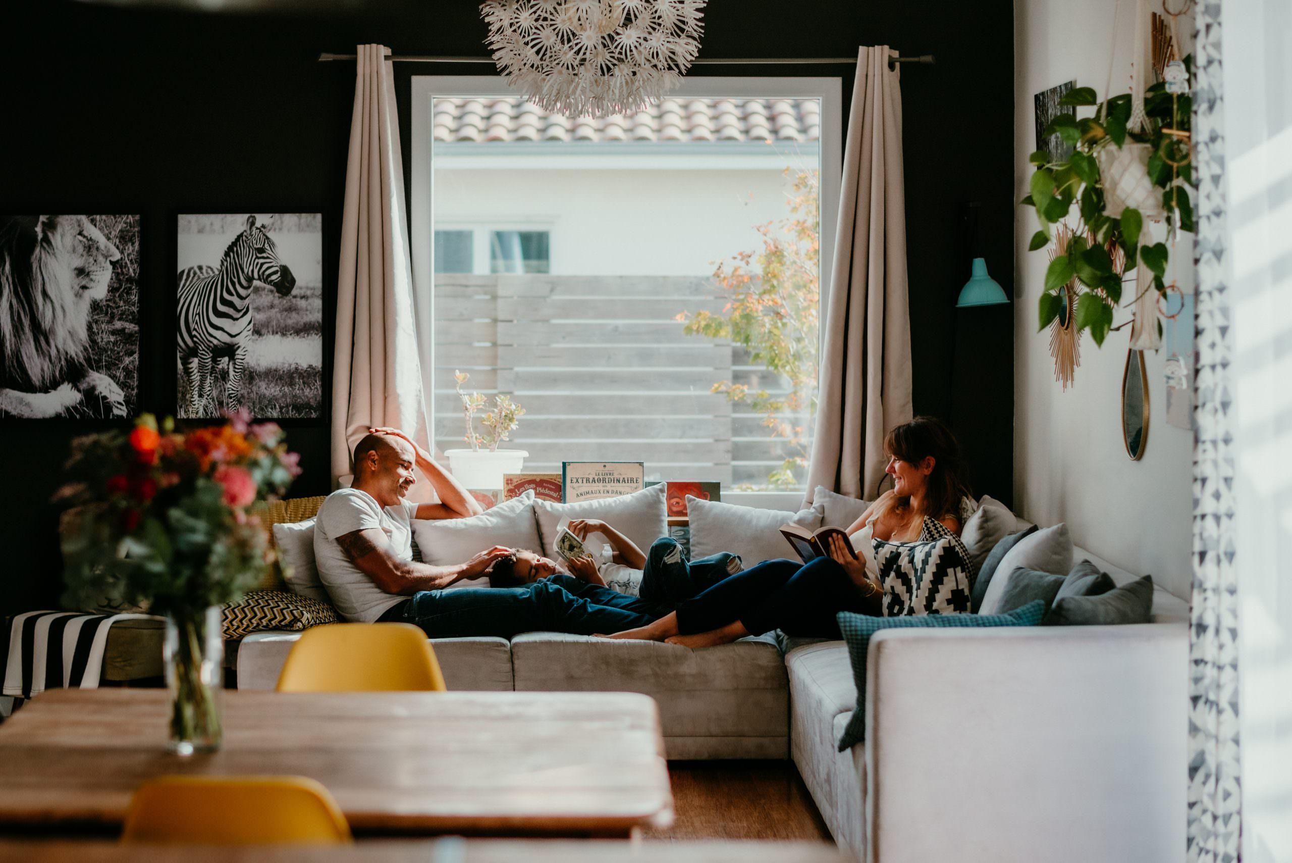 portrait de famille confortablement installe sur son canape dans leur salon