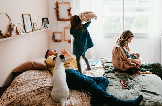 enfant debout sur le lit bataille de coussins avec papa maman allaite son nouveau-ne